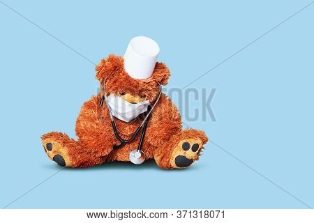 Tired Teddy Bear Doctor With Protective Medical Mask And Stethoscope On Blue Background. Teddy Bear