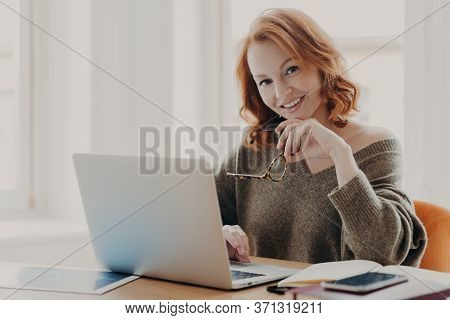 Pleased Female Scientist Makes Research On Laptop Computer, Poses In Coworking Space, Searches Infor