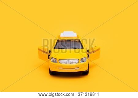 Urban Taxi And Delivery Service Concept. Toy Yellow Taxi Car Model. Copy Space For Text, Banner. Onl