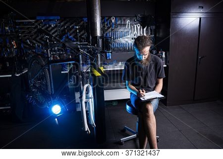 Bicycle Workshop Technician Doing Administrative Work. Bicycle Mechanic Writing In His Checklist Not