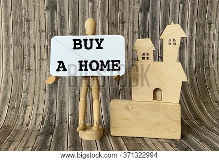 Wooden Man Holding A White Paper With The Inscription Buy A Home , Next To A Wooden House On A Woode