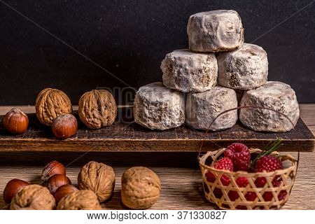 French Cheese Crottin De Chavignol In The Dark Background. Composition With Hazelnuts, Walnuts, Rasp