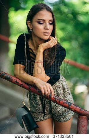 Cute Brunette Girl Looks Looks Aside, Edging Her Hands Against The Handrail, The Pipe. Beautiful Bro