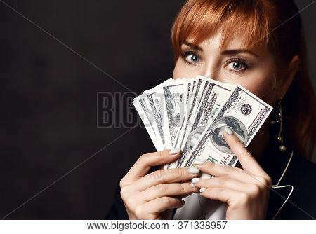 Portrait Of Young Beautiful Red-haired Business Woman In Black Formal Jacket Holding Heap Of Dollars