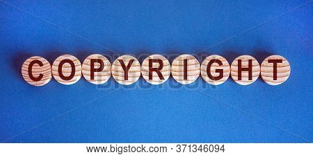 Wood Circles With Word 'copyright' On Blue Paper, Copy Space. Business Conceptual Image.