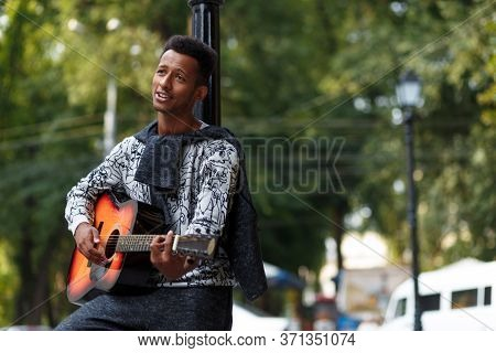 Cheerful Young Musician Played On Guitar, Sing A Song Outside In Sunny Day, Isolated On A Blurred St