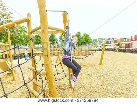 Selective Focus. The Girl Climbing And Sliding On Slide In The Playground. Happy Children Playing An