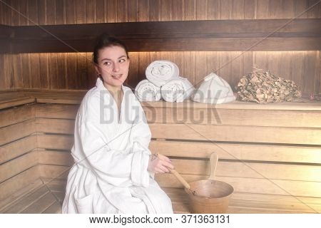 Beautiful Young Woman In A White Coat Is Relaxing In A Sauna. Sauna Made Of Wood. Concept: Relaxatio