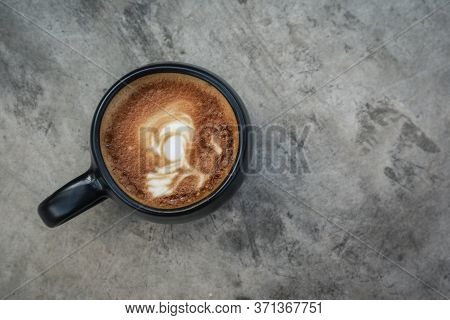 A Cup Of Coffee With Latte Art On Top In Black Mug On Grey Concrete Background, Top View
