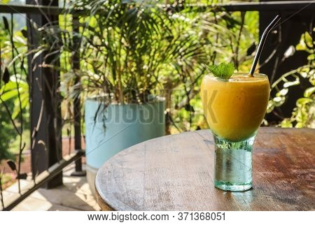 Mango Juice In Glass With Metal Drinking Straw On Table In Tropical Cafe