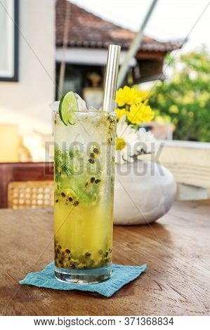 Passion Fruit Mojito Cocktail With Metal Drinking Straw On Wooden Table In Cafe.