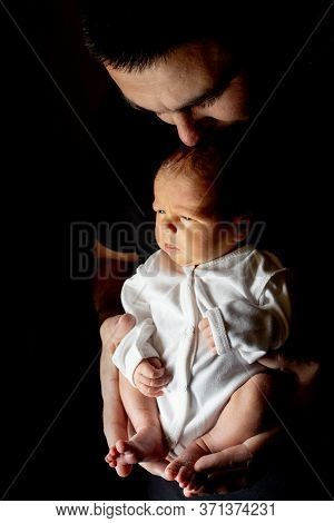 Father Holding His 15 Days Old Son In His Hand On Black Background. Baby Lying On His Father