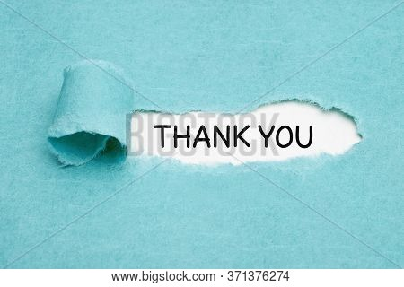 Handwritten Text Thank You Appearing Behind Ripped Blue Paper. Appreciation, Gratefulness, Or Thankf
