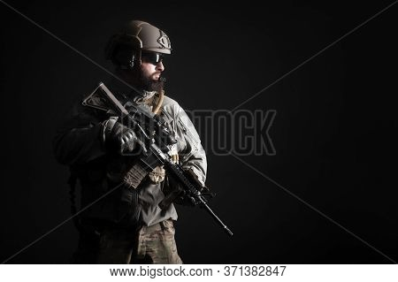 Portrait Of A Special Forces Soldier In Uniform With A Weapon Against A Dark Background, Elite Troop