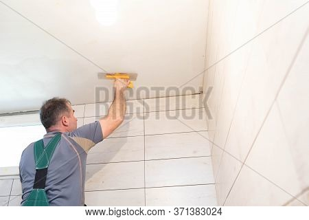 The Worker Applies Plaster On The Ceiling Of The Renovated Bathroom. Construction Worker In Middle A