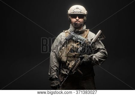 Usa Soldier In A Military Suit With A Rifle Against A Dark Background, An American Commando With A G