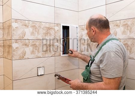 The Plumber Begins Repair Work On The Water Distributor To Adjust The Pressure. A Professional Worke