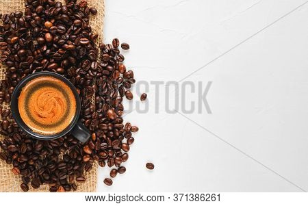 Fresh Roasted Coffee Beans And A Cup Of Hot Espresso With Froth, Located On The Left On A Wide Concr