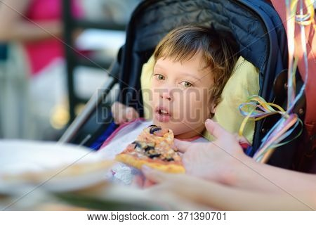 Mother Feeding An Pizza A Little Disabled Girl In A Wheelchair. Child Cerebral Palsy. Inclusion. Dis