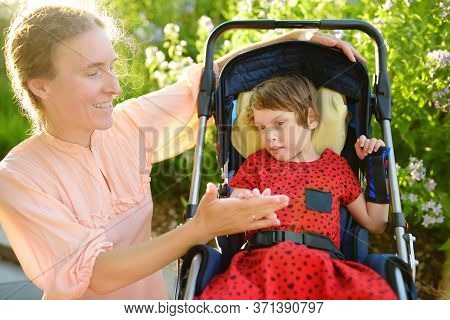 Woman With Disabled Girl In A Wheelchair Walking In The Summer Park. Child Cerebral Palsy. Disabilit