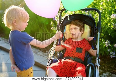 Communication Of Boy And A Disabled Girl In A Wheelchair Walking In The Park Summer. Brother Hands B