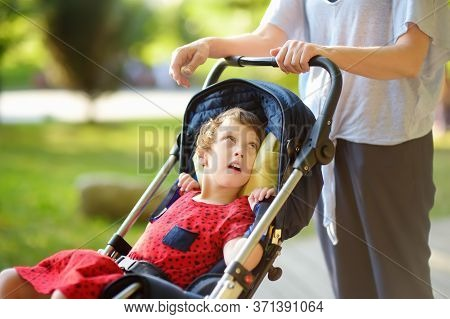 Woman With Disabled Girl In A Wheelchair Walking In The Park Summer. Child Cerebral Palsy. Disabilit