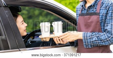 Waiter giving hot coffee cup disposable tray and bakery bag through car window to customer at drive thru service station. Drive thru is popular service after coronavirus covid-19 pandemic. Panoramic.