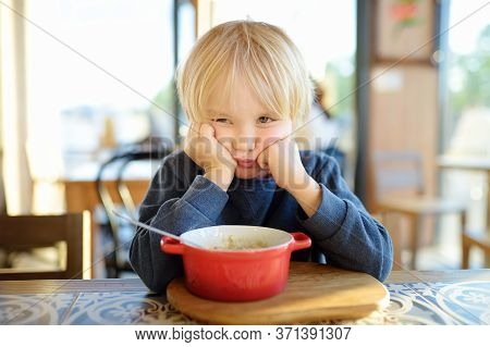 Little Child Sitting The Table In Cafe Or Restaurant And Doesn't Want To Eat. Healthy Food. Kids Die