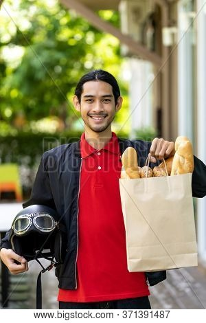 Portrait of attractive and smile asian deliverly bike man holding grocery bag from supermarket ready to deliver to online customer. Food deliverly and online order concept.