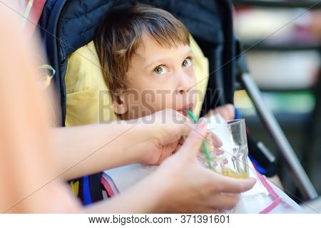 Mother Giving Disabled Child A Drink. Cute Little Girl Sitting In Wheelchair. Child Cerebral Palsy.