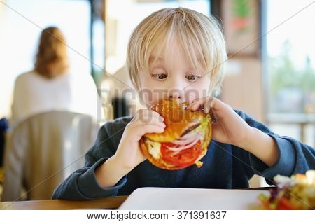 Cute Blonde Boy Eating Large Hamburger At Fast Food Restaurant. Unhealthy Meal For Kids. Junk Food.