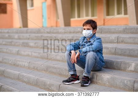 Schoolboy In Protective Mask In Jeans Clothes, Black Trainers, Sits On Stairs Outdoors In Schoolyard