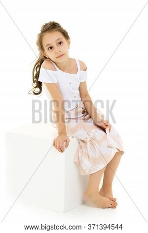Thoughtful Beautiful Girl Sitting On White Cube, Portrait Of Cute Preteen Girl Wearing Blouse And Be