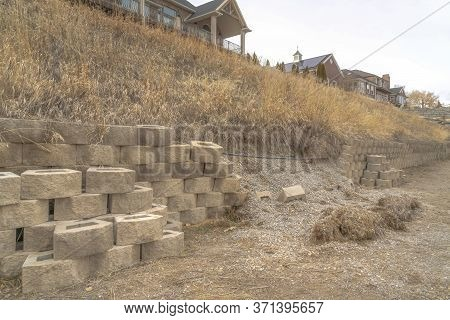 Damaged Stone Blocks Retaining Wall Lining A Hill With Homes Under Cloudy Sky
