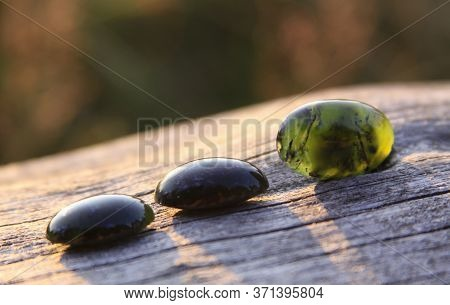 Black Jade Translucent Green Stone In Sunlight On Wood. The Black Jade Is Dark Green In Color, But U