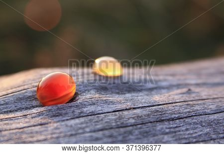 Two Red And Creamy Yellow Chalcedony Agate Gemstones On Wooden Background Shining In The Sunlight. C