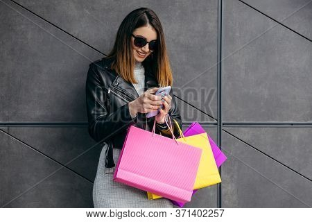 Skinny Pretty Young Woman With Shopping Bag Stay On Gray Background Near The Mall Smiling And Using