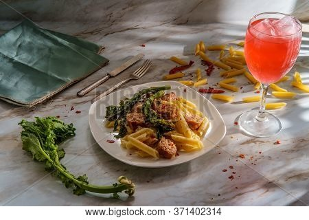 Italian Spicy Sausage Penne Pasta And Broccoli Rabe With Dramatic Lighting From Window