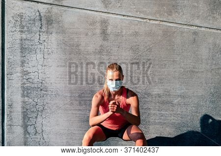 Front View Of Fit And Healthy Caucasian Woman With Protective Mask Working Out Outdoors Doing Jumpin