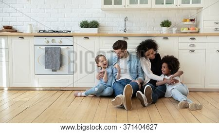 Multinational Homeowners Family With Daughters Sitting In Modern Kitchen Floor