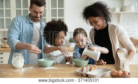 Full Multi Ethnic Family Cooking Pancakes Together In Modern Kitchen