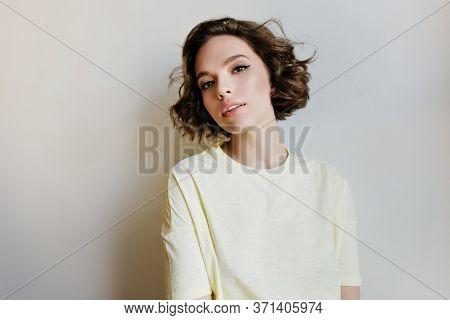 Happy European Female Model With Dark Short Hair Enjoying Indoor Photoshoot. Studio Shot Of Dreamy C