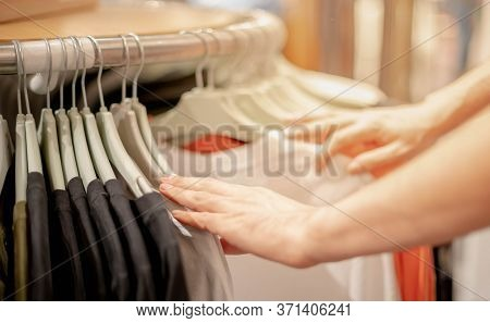 Male Hand Choosing Clothes For Checked Pattern Cotton Dress On The Rack In Cloth Shop At Cloth Shop