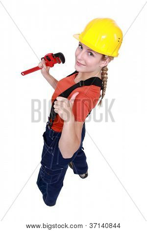 Tradeswoman giving the thumb's up and holding a pipe wrench