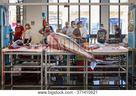 Sicily, Italy - May 23, 2020: Fish market in Riposto, Sicily. People wearing medical masks against coronavirus during Covid-19 pandemic in Italy