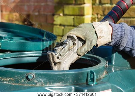 Closeup Of Man Filling A Bunded Oil Tank With Domestic Heating Oil (kerosene) At A House In Rural En