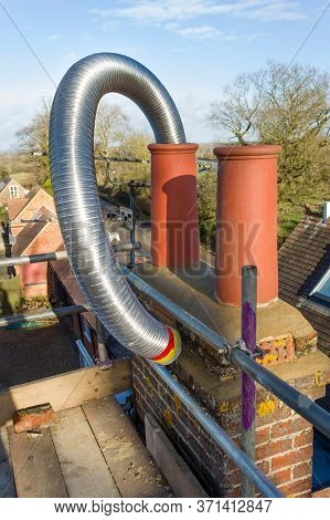Installing A Flexible Steel Flue Liner Into A Chimney During A Wood Burning Stove Installation, Uk