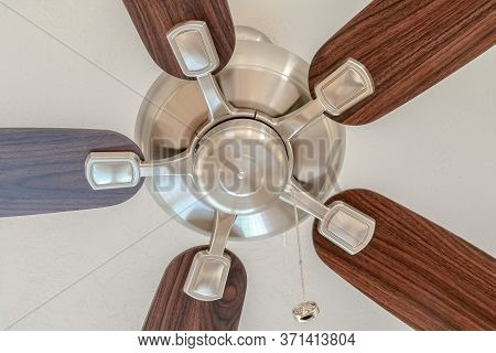 Ceiling Fan With Wooden Blades And Lights Mounted On The Ceiling Of A Home
