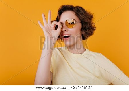 Close-up Photo Of Adorable Pale Girl In Yellow Sunglasses. Blissful Lady With Short Haircut Fooling