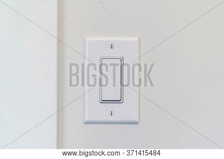 Electrical Rocker Light Switch With Flat Broad Lever On White Interior Wall